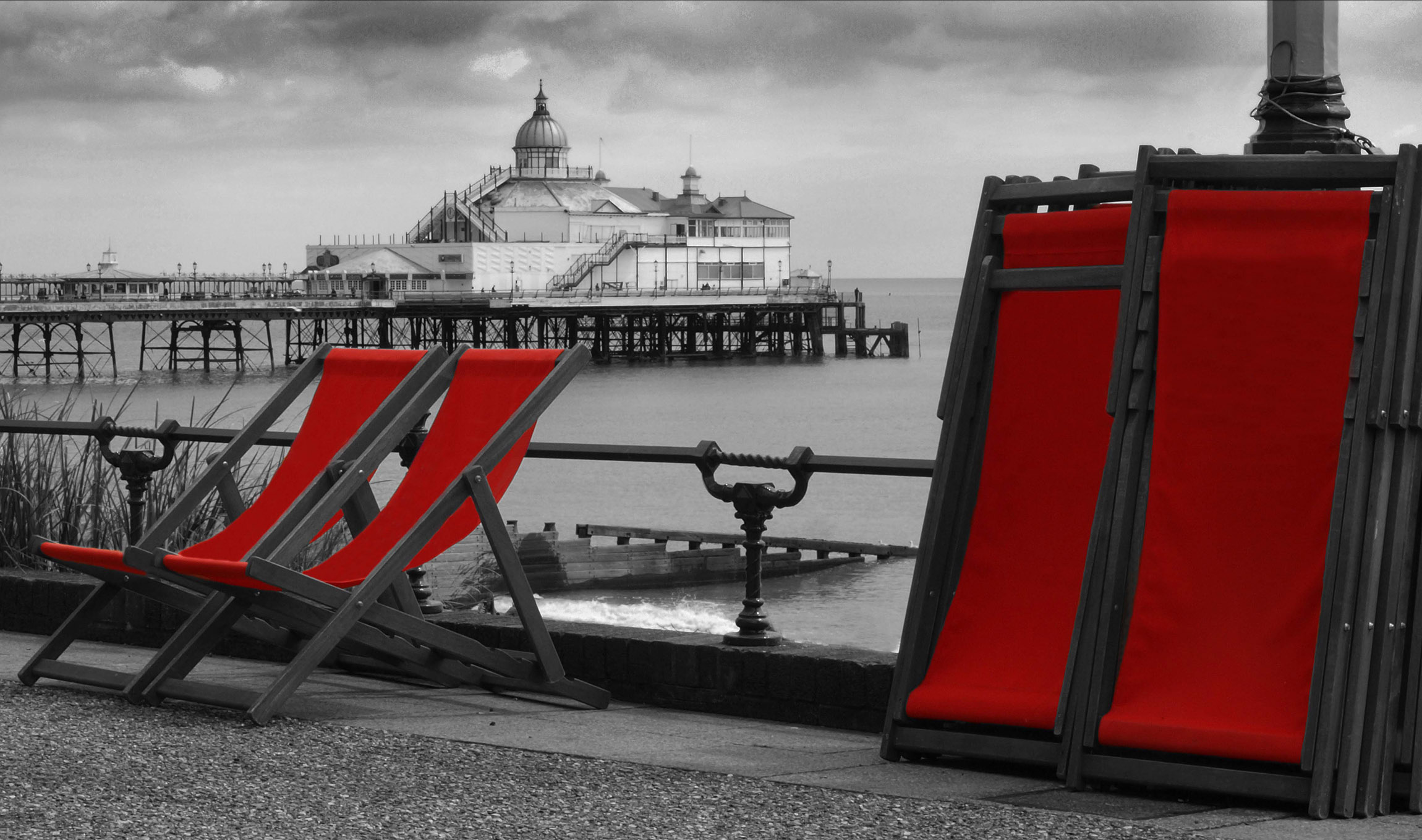 Enhanced black and white photograph of Eastbourne pier in the centre with a foreground of the promenade, two deckchairs ready for seating and several stacked deckchairs. All deckchair covers are picked out in blood red. © Copyright 2014 Andy Huntley photography